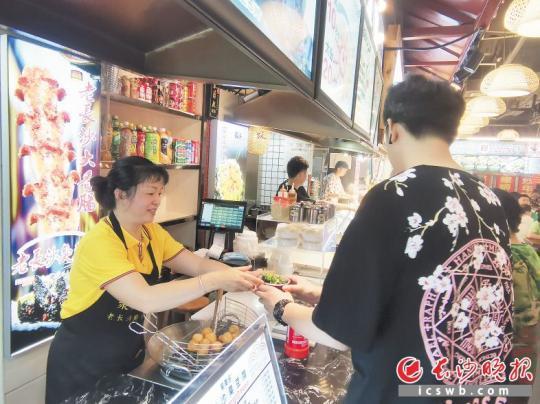 刘艳(左)向顾客端上自制臭豆腐。长沙晚报全媒体记者 王斌 摄