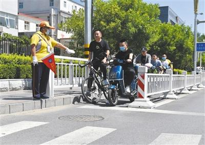 <b>北京朝阳区飞机场辅道和大山子街口文明引导员提示骑车人在斑马</b>