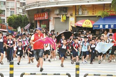 他在校门口义务指挥交通 五年风雨不改护送小学生过马路