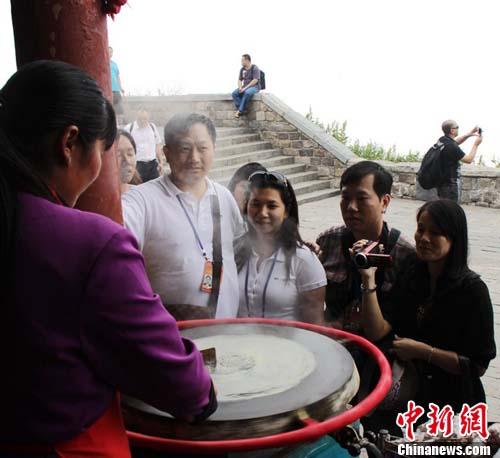 华裔青年登泰山时,驻足观赏泰山煎饼制作过程