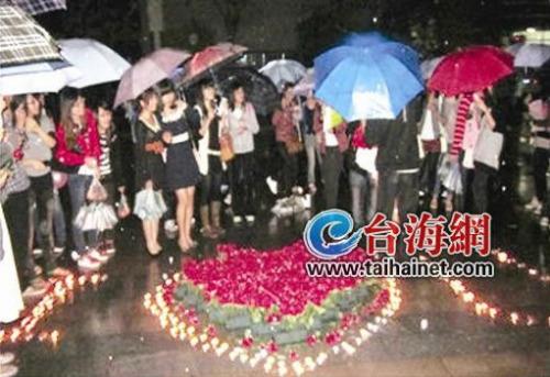 男主角站在心形玫瑰花丛前向女主角表白,引来许多学生的围观-男生