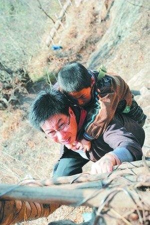 12名学生每周需要护送上下天梯,对年龄小的孩子李桂林要背着图片