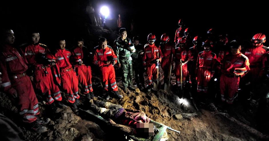 救援队员脱帽向遇难者致哀