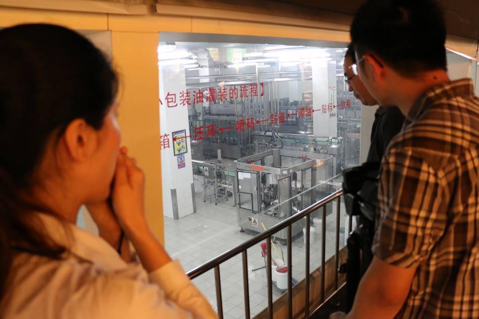 媒体团参观金龙鱼小包装油灌装过程