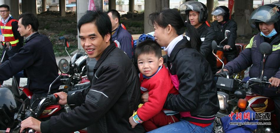 拖家带口骑摩托车返乡的农民工