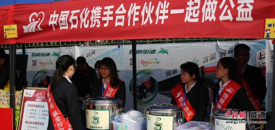 工作人员为过往农民工提供免费热水