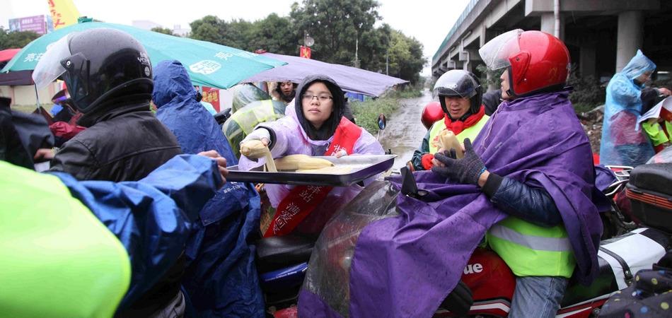风雪中,志愿者为返乡人员送水送食