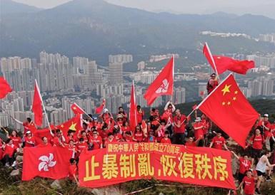 香港市民爬上狮子山顶挥舞国旗、区旗