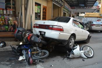大马华人老妇开车慌张连发车祸压住3辆摩托(图)
