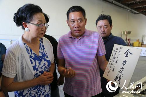 中国侨网刘磊(中)向方李邦琴(左)以及参观者展示抗战实物。(人民网/韩莎莎 摄)