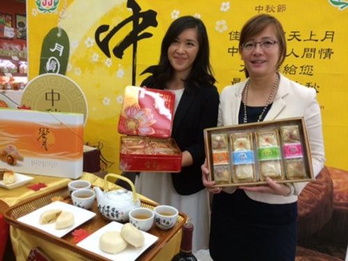 大华发言人谭敏毅(右)和市场部Teresa梁(左)4日展示各种月饼。(美国《世界日报》/杨青摄影)
