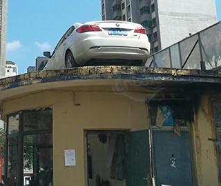 私家车堵小区门 物业用将它吊上房顶