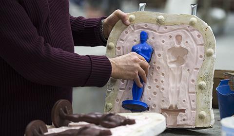 当地时间1月13日,在美国纽约一家铸造厂,一名工作人员拿着奥斯卡小金人,这是一座24K镀金铜像。