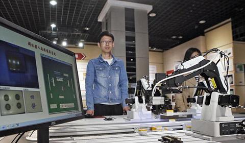 """""""硕果酬壮志 群星耀苍穹""""西安交大教学科研获奖成果展在西安交大博物馆开幕。一边抓麻将牌一边喊着""""二饼""""的机器人吸引了很多人的目光。"""