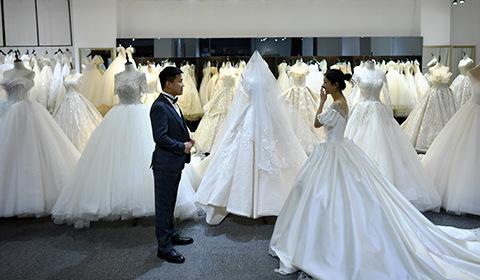 """4月8日,河北石家庄一对准新人正试穿婚纱和礼服。据了解,往年此时多为结婚旺季,今年受疫情影响,很多""""新人""""延期举办婚礼。"""