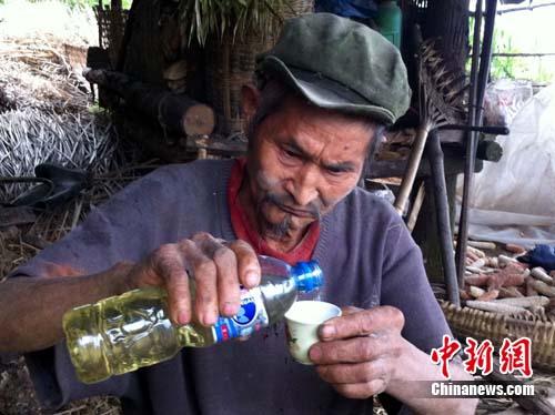 重庆 陈德均/陈德均正在将汽油倒入杯中,准备饮用。...