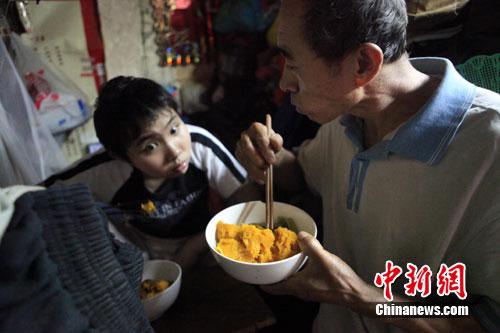 韦亮/父女俩的午餐是煮南瓜,南瓜是爸爸从附近早市上捡来的。韦亮摄...