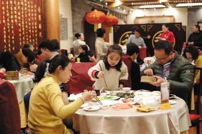 除夕夜,在餐厅内吃年夜饭的一家人.新京报记者 侯少卿 摄