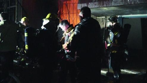 小区起火瘫痪老人被困消防员救人致自己被玻璃划伤