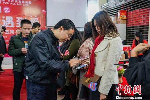 图为2月17日,在一场相亲活动现场,参与的男女互扫微信留下联系方式。中新社记者 陈冠言 摄