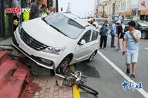 新手司机驾新车撞人后冲上四级阶梯