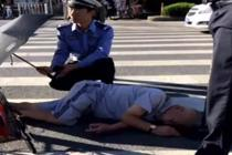 老人摔倒路口 警民接力撑伞遮阳