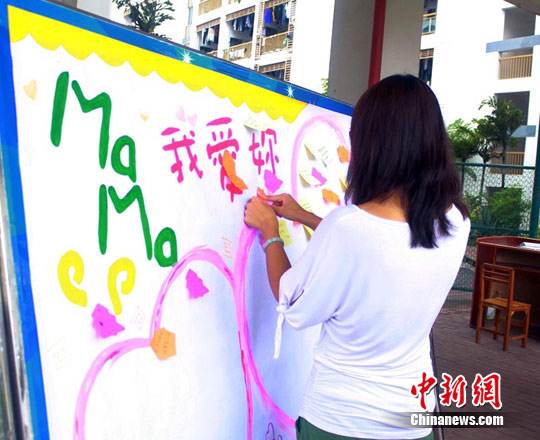 图为活动现场大学生在心愿展板上写祝愿