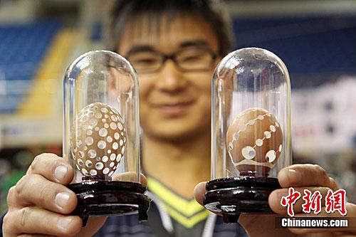 作品 韦亮/图为一名大学生展示蛋壳雕刻艺术作品。中新社发韦亮摄