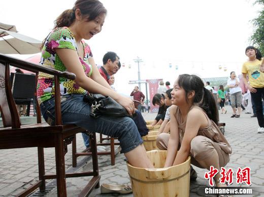 今第一次为妈妈洗脚的胡关鑫雨.   摄-重庆端午节孩子为父母洗脚表