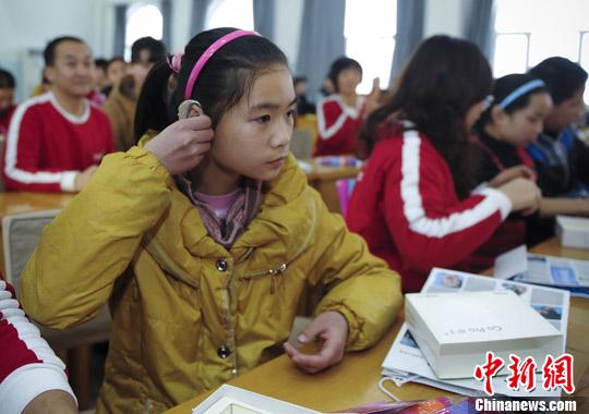 12月22日,乌鲁木齐市聋人学校一名聋哑学生正在佩戴专业助听器.
