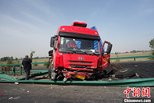 事故现场一辆货运大车的车体因撞击翻倒在高速路的北侧路面,将高速路