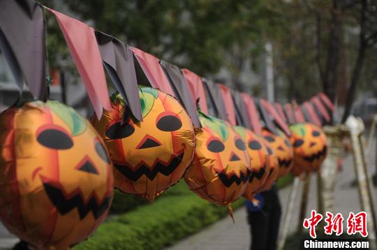 重庆/10月28日,重庆街头挂起了一串串的南瓜鬼脸恐怖表情。