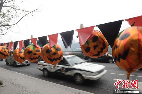 重庆 陈超/图为重庆街头树上挂起了南瓜鬼脸恐怖表情。陈超摄