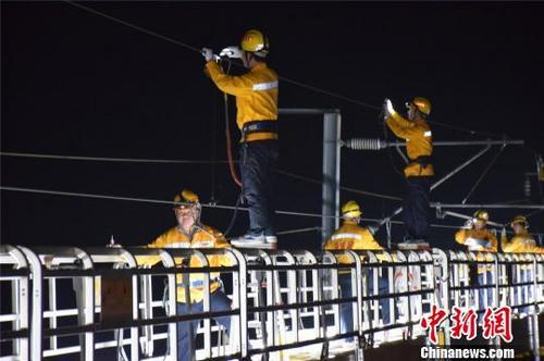1月25日,接触网维修第2小组职工在检修列平台上作业。 申卫平 摄