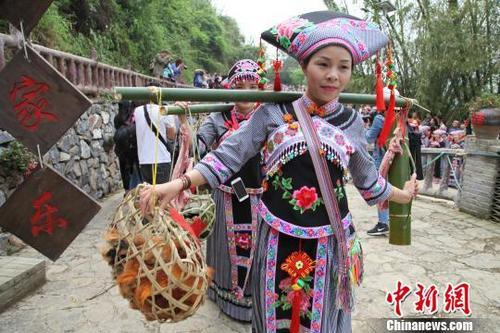"""4月7日,廣西百色布林村舉辦山歌節慶祝傳統節日""""三月三""""。圖為姑娘出嫁情境展示。 楊志雄 攝"""