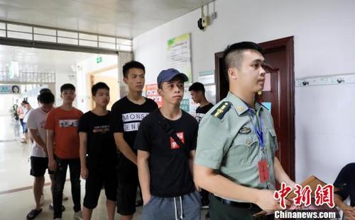 适龄大学生在广西柳州市融安县人民医院征兵体检站接受外科方面的检查。 谭凯兴 摄