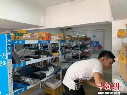 一位学生正在摆满了快递的货架上找寻自己的快递。 王以照 摄