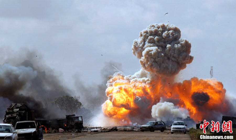 军事打击。图为3月20日,利比亚城市班加西附近车辆