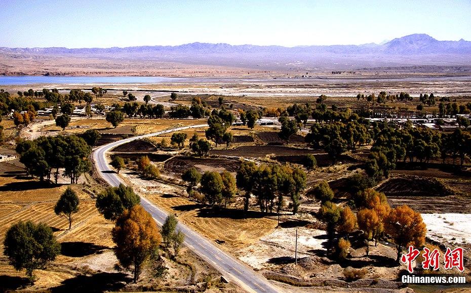 甘肃 玉门/一条乡村公路在农田中蜿蜒,而远处的群峦也是叠嶂的,在山与田...