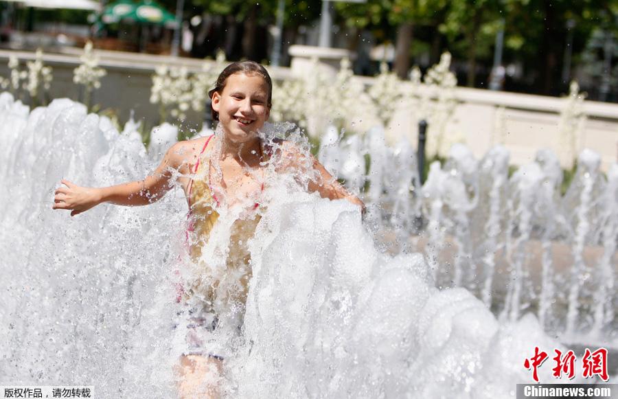 达佩斯,女孩在喷泉里玩耍,当天气温达到35摄氏度.-热浪来袭 世