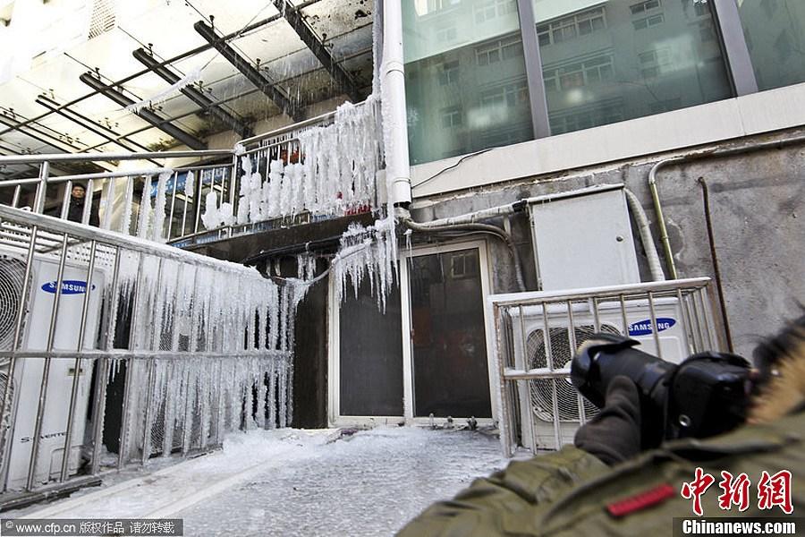 但清水不断从楼上的下水管流出,流到台阶上再次结冰.