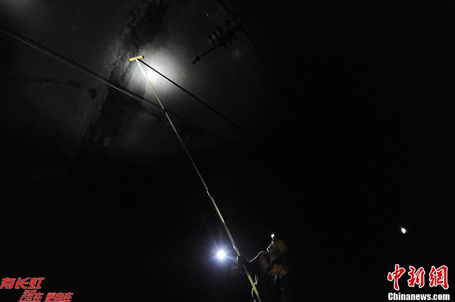 12月12日,陇海铁路线天兰段的松树湾隧道中随处可见的冰棱挂在隧道壁上,王晓毅和他的工友们冒着冬日的严寒在这里清理着冰棱,他们是兰州铁路局兰州供电段的职工,从每年的11月开始到来年的4月底,他们就一直要在隧道中打冰,到最冷的时候他们一天要进隧道打3次冰。王晓毅说冰要及时打,不及时打冰棱就会碰到电力接触网,这样就会造成跳闸,影响铁路正常运行。由于陇海线车流密度大,不能落实停电除冰的时间,他们只能步行巡视除冰。杨艳敏 摄