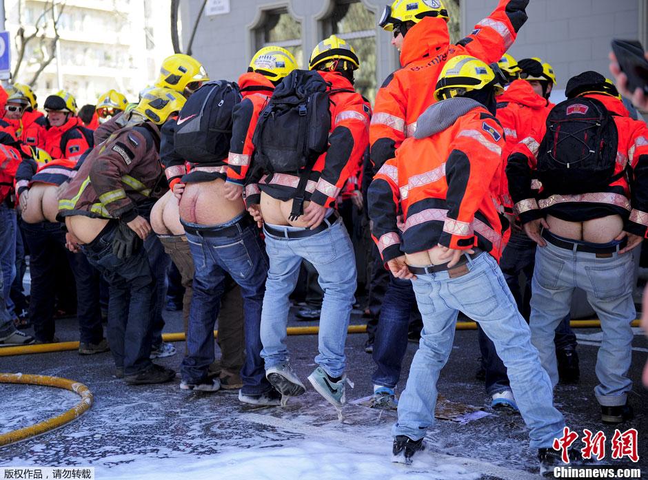 西班牙消防员街头抗议 露屁股喷泡沫大战