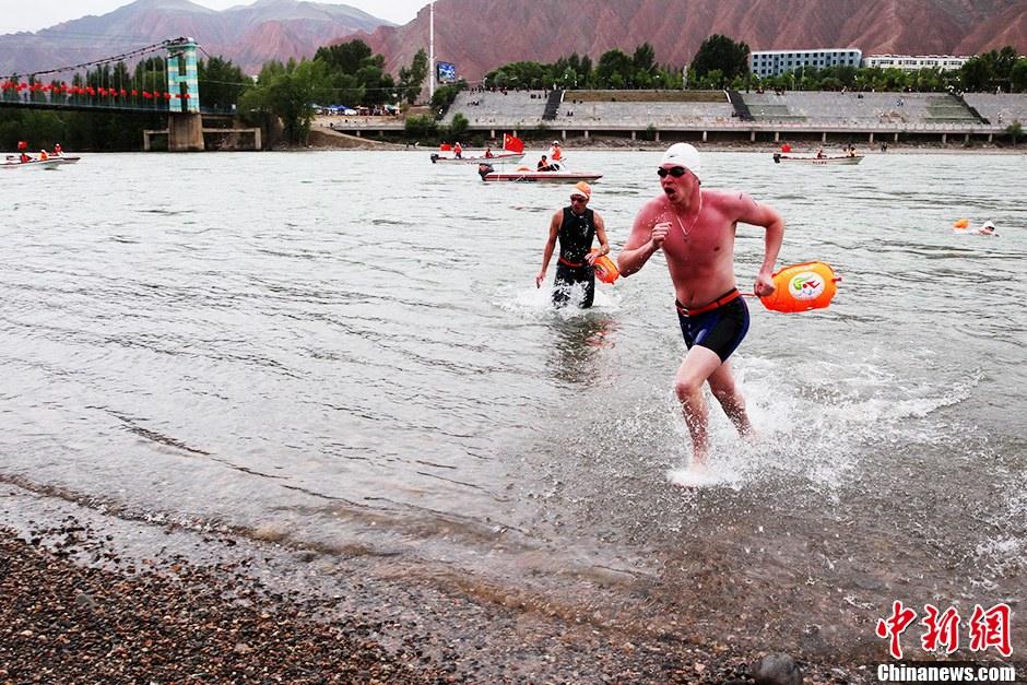 6月16日9时30分,第九届中国青海(循化)国际抢渡黄河极限挑战赛决赛在青海省循化撒拉族自治县波浪滩举行,共有60名选手参加决赛。黄河极限挑战赛是目前中国黄河上游第一个在海拔高、水温低、水流急、氧气稀薄的世界第三极举办的公开水域大型国际赛事。本届赛事共有来自中国、加拿大、美国、斯洛伐克、德国、俄罗斯、比利时等15个国家34支代表队参赛。图为来自俄罗斯的参赛选手霍达科夫斯基爱德华(右一)向终点发起最后冲刺。中新社发 胡贵龙 摄