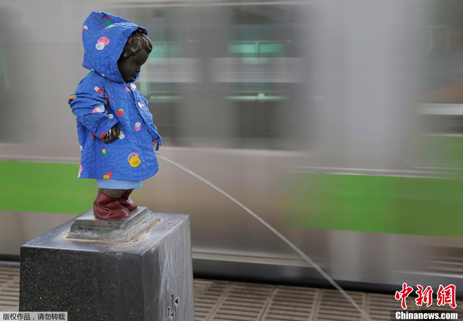 雨季来临 东京撒尿男孩雕塑穿雨衣 中新网