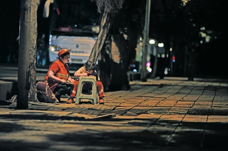 图为路灯下小女孩正在读书.马代国 摄-环卫妈妈路灯下边扫地边辅导