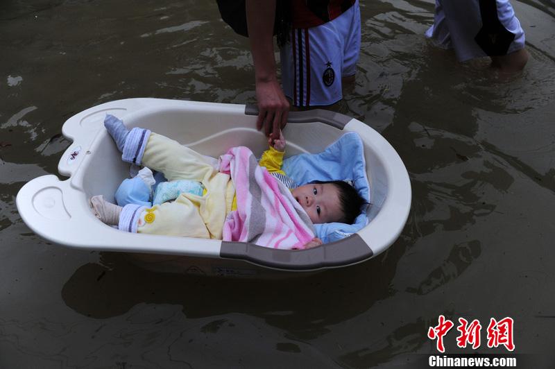 淡定宝宝洗澡盆当船躺 余姚一男子携妻带子走出洪水