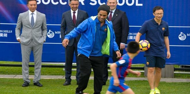 罗纳尔迪尼奥空降海口 冒雨与小球迷踢球互动