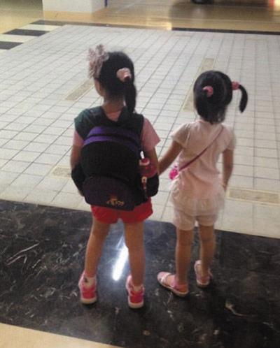 俩女儿背书包手拉手背影温馨-中新