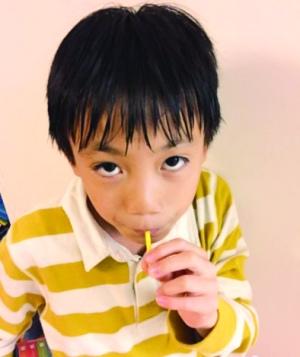 照片中,张艺谋儿子吃着棒棒糖,抬头看镜头,一头大汗,模样可爱.